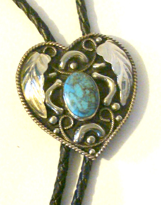 The turquoise Stone Heart Shaped silver Bolo Tie is a beautiful sterling silver plated heart shaped cowboy neck tie with a raised silver leaf and a red stone center to add a southwestern flare that will dress up any cowboy or cowgirl shirt.