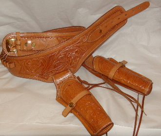 This .38 Natural Tooled Leather Cowboy Western Double Gun Holster holds any 38 hand gun and fits 6 or 8 inch barrels with floral hand tooled leather and back waist bullet holes for a cowboy action shooting western event.