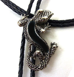 This Black Lizard Silver Bolo Tie is made in the USA with long detailed lizard filled with black enamel on a black bolo string great on a cowboy shirt.