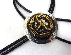 The Gold Plated Barbed Wire Longhorn Silver Western Bolo Tie made of gold plating with a round southwestern concho on a black bolo that will dress up any cowboy or cowgirl shirt.