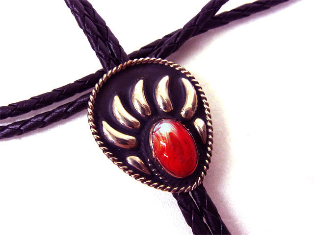 The Red Stone Silver Raised Bear Claw Bolo Tie is a beautiful sterling silver plated large bolo in a bear claw design with a red center stone and black enamel that will dress up any cowboy or cowgirl shirt.