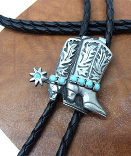 The Silver Double Cowboy Boots Turquoise Bolo Tie is a beautiful sterling silver plated large bolo with turquoise stones and spur accents that will dress up any cowboy or cowgirl shirt.
