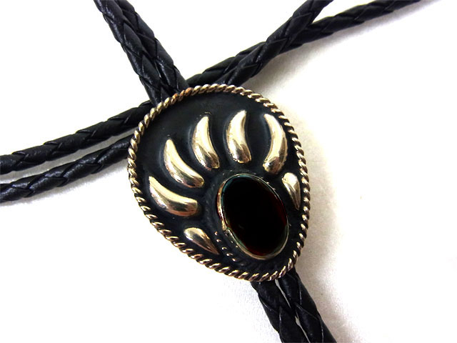 The Blackend Silver Onyx Stone Bear Claw Bolo Tie is a beautiful sterling silver plated large bolo in a bear claw design with a black stone center stone and black enamel that will dress up any cowboy or cowgirl shirt.