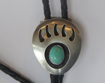 The Silver Bear Claw Turquoise Bolo Tie is a beautiful sterling silver plated large bolo in a bear claw design with a turquoise center stone and black enamel that will dress up any cowboy or cowgirl shirt.