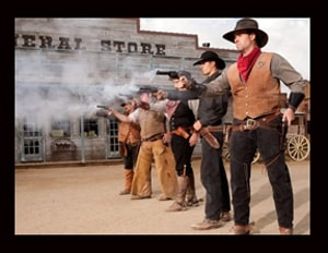 The Wild Cowboy carries Antique and tooled Leather 38 and 45 Caliber Single and Double Gun Holsters with old west brown black tooled or antique frontier leather with bullet holes for a cowboy action shooting 1800's frontier western style event.